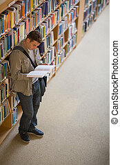 Student reading a book standing in library
