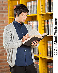 Student Reading Book By Shelf In Library