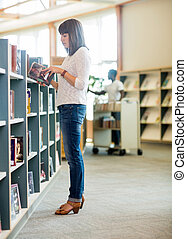 Student Reading Book In Bookstore