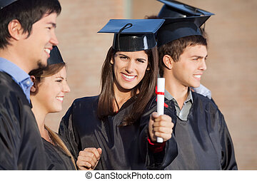 Student Showing Diploma While Standing With Friends At College