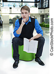 Student sit on stool with opened book