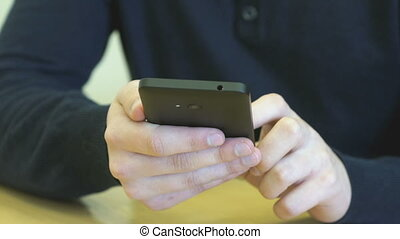 Student sitting at the desk holds the smartphone