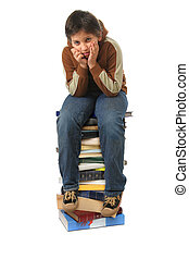 Student sitting on a pile of books - Boy sitting on a big...