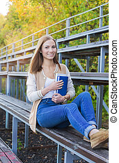 Student sitting on sport tribune and smiling at camera