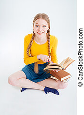 Student sitting on the floor with book