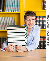 Student Sitting With Piled Books In University Library