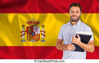 Student smiling over Spanish flag