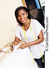 Student smiling seamstress cutting a paper.