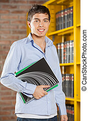Student Smiling While Holding Books In College Library