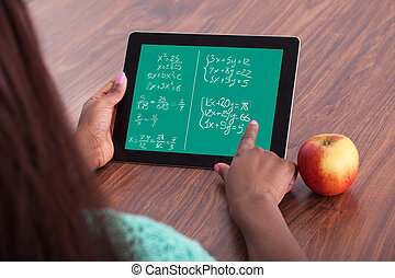 Student Solving Math Problems On Digital Tablet