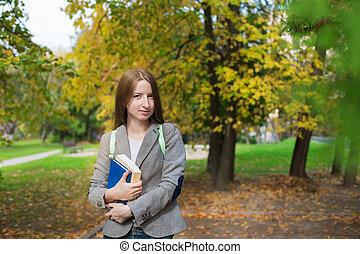 student, staand, met, boek, in, herfst