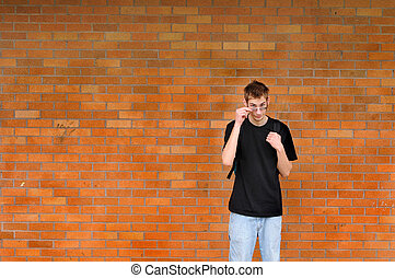 Student standing in front of brick wall