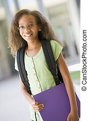 Student standing outside school holding binder and smiling (selective focus)