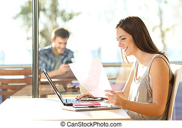 Student studying in a coffee shop - Side view of a beautiful...