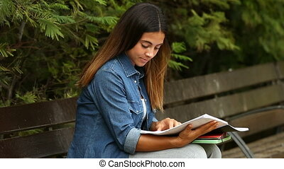 Student studying in a park - Student girl studying in a park...