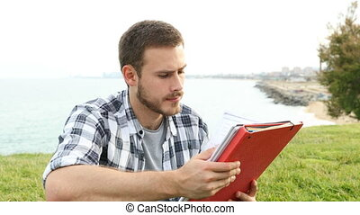 Student studying memorizing notes outdoors - Serious student...