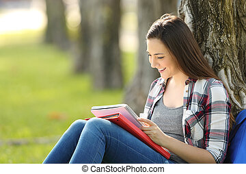 Student studying reading notes outside