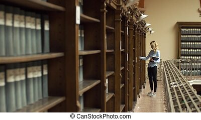 Student takes book from shelves in the library