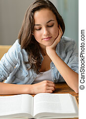 Student teenage girl reading book at home