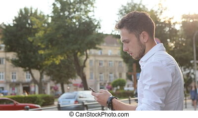 Student texting a message on phone in the city center.