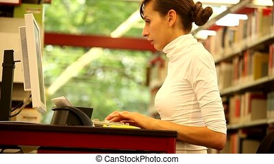 student typing - female student working in library