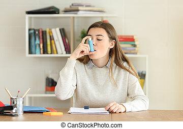 Student using an asthma inhaler at home