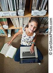 Student using laptop against bookshelf on the library floor
