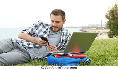 Student using smart phone lying on the grass - Distracted ...