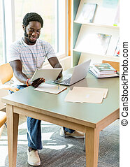Student Using Technologies While Studying In Library