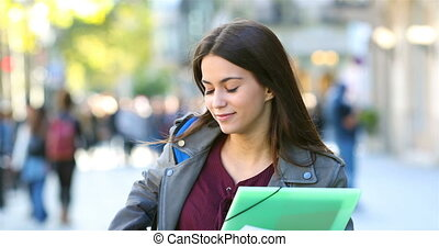 Student walking and checking phone in the street - Happy...