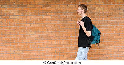 Student walking besides brick wall