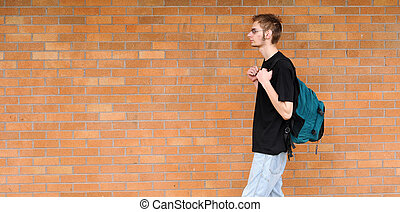 Student walking besides brick wall - A tall white Caucasian...