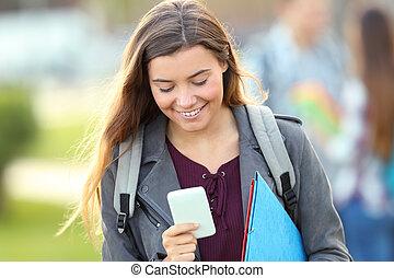 Student walking towards camera using phone