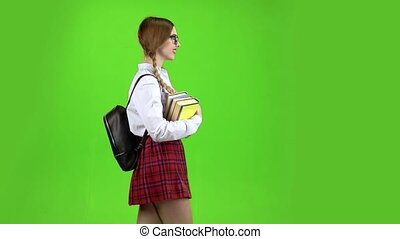 Student walks with a backpack on her back and carries books in her hands. Green screen. Slow motion. Side view