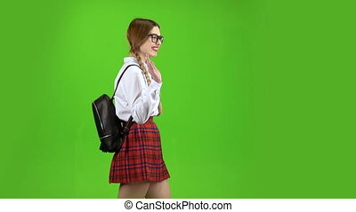 Student walks with a backpack on her back and waves her greetings. Green screen. Slow motion. Side view