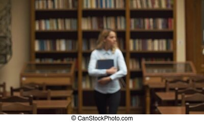 Student walks with large book in the library