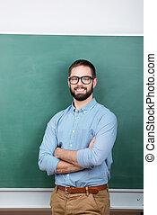 Student Wearing Eyeglasses Against Chalkboard