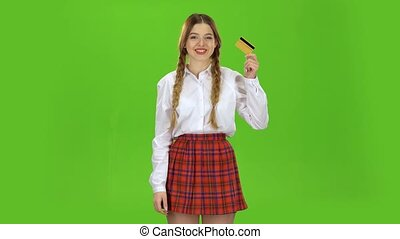 Student with a credit card in her hands is happy. Green Screen