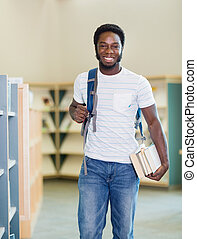 Student With Backpack And Books In Library