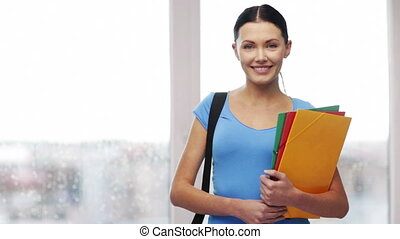 student with bag and folders showing thumbs up