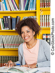 Student With Books And Pen Looking Away In Library