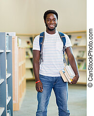 Student With Books Standing In Bookstore