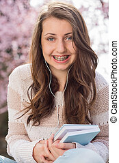 Happy teenage student with braces holding book outside