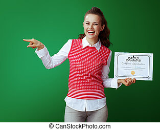 student with Certificate of Graduation pointing at something