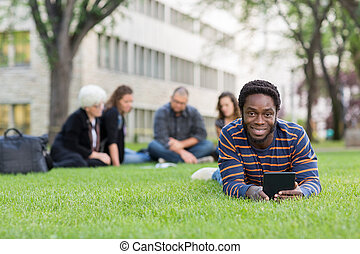 Student With Digital Tablet On Grass At Campus Park