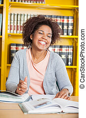 Student With Eyes Closed Sitting At Table In Library