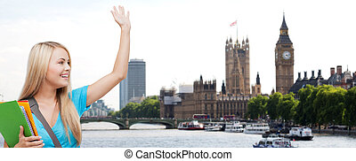 student with folders waving hand over london city -...