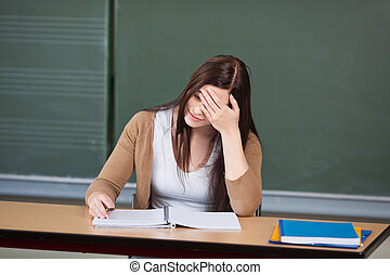 Student With Hand On Head Sitting At Desk Against Chalkboard