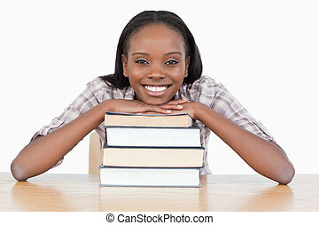 Student with her chin on a stack a book against a white ...