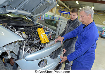 student with instructor repairing a car during...